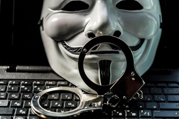 Maschera ananimus con manette sul portatile con tastiera. foto di alta qualità