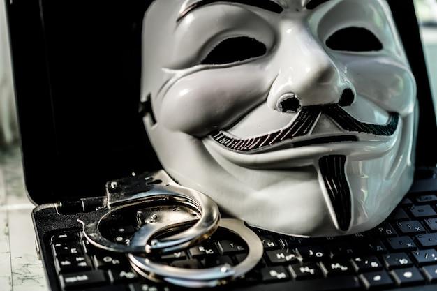 Maschera ananimus con manette sulla tastiera del laptop. criminalità hacker. foto di alta qualità