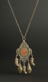 Antico ciondolo antico con pietre su sfondo nero. gioielli vintage dell'asia centrale