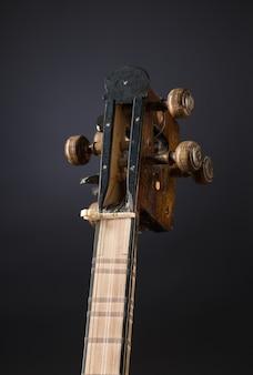 Antico strumento musicale a corde asiatico su sfondo nero con retroilluminazione. pirolo