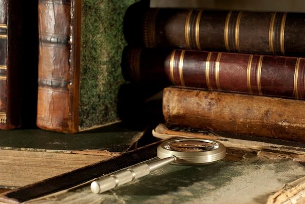 Un libro antico con una copertina frastagliata e una lente d'ingrandimento su un tavolo