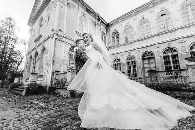Antico edificio con finestre ad arco lo sposo abbraccia la sposa e loro sorridono