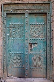 Antica porta scolpita con incisioni di un'antica casa di fango in oman