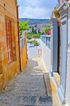 Antica città greca di lindos. vista dai piedi dell'acropoli. strada stretta della città di lindos
