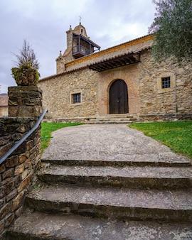 Antica chiesa medievale in pietra con scala di accesso e torre con balcone. horcajuelo madrid. spagna.