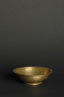 Antica ciotola di metallo su sfondo scuro. stoviglie in bronzo antico