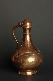 Antica brocca di metallo orientale su sfondo scuro. stoviglie in bronzo antico