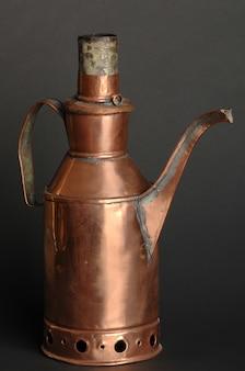Antica teiera in metallo orientale su sfondo scuro. stoviglie in bronzo antico