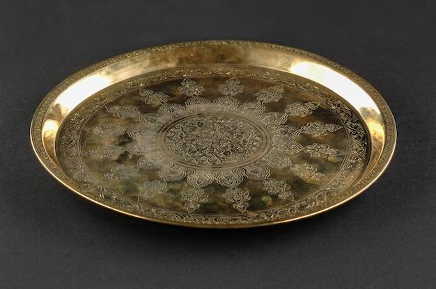 Vassoio di metallo orientale antico su sfondo scuro. stoviglie in bronzo antico