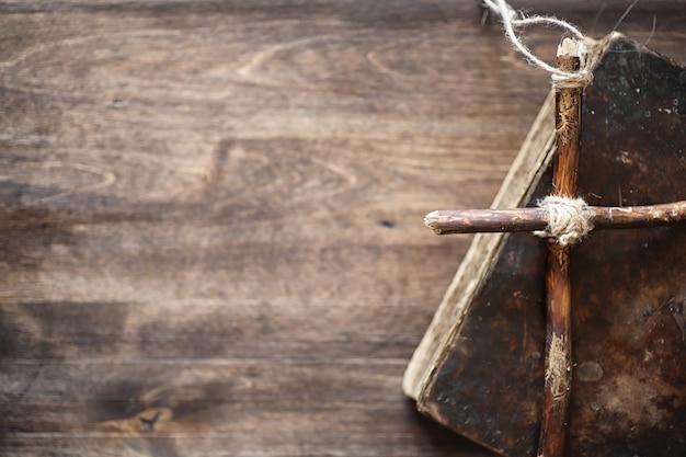 Antico libro religioso e croce di legno sullo sfondo di un legno e tela