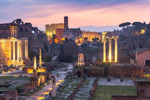 Antiche rovine di un foro romano o foro romano, colosseo o colosseo all'alba a roma, italia. vista dal campidoglio