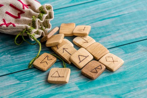 Rune antiche, borsa di tela con ricami su fondo in legno vecchio vintage. messa a fuoco selettiva.