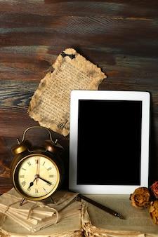 Cose antiche e tablet sulla tavola di legno