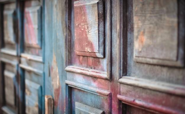 Primo piano della porta di entrata dipinto trascuratamente strutturato strutturato di legno antico.
