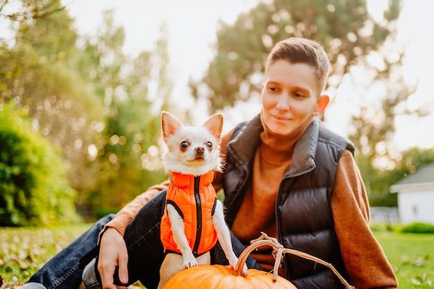 Una ragazza androgina con un taglio di capelli corto tiene in braccio un cane chihuahua con un giubbotto arancione. foto di alta qualità