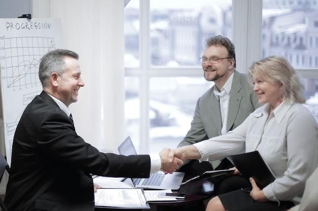 Andshake di un uomo d'affari e di una donna d'affari durante una riunione in ufficio