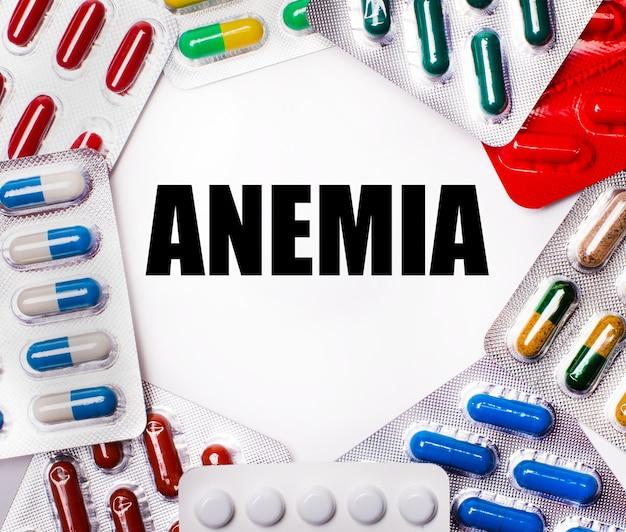Anemia è scritto su uno sfondo chiaro circondato da confezioni multicolori con pillole. concetto medico