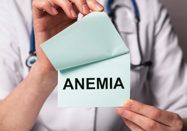 Testo di anemia su carta nelle mani del medico