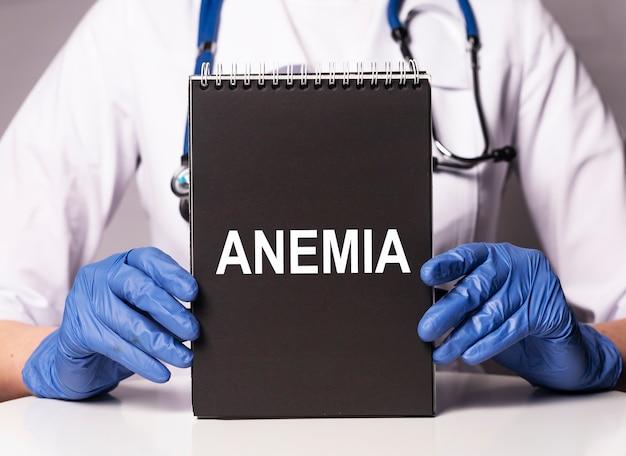 Parola di anemia su carta nera nelle mani del medico in guanto blu