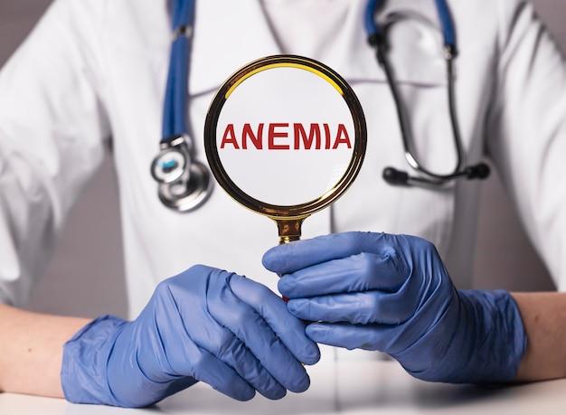 Parola di anemia in mano del medico attraverso il primo piano della lente d'ingrandimento