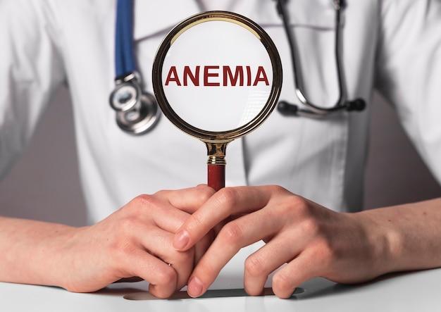 Parola di anemia in mano del medico attraverso la lente d'ingrandimento