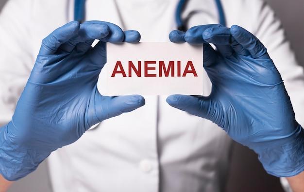 Parola di anemia su carta in mano del medico in guanti da vicino