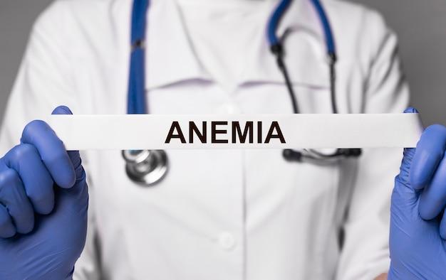 Parola di anemia su nastro di carta nel concetto di diagnostica della malattia del sangue della mano del medico