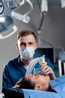 Anestesista che fa anestesia di ingalazione per il paziente. il medico mette una maschera sul paziente prima di iniziare l'operazione