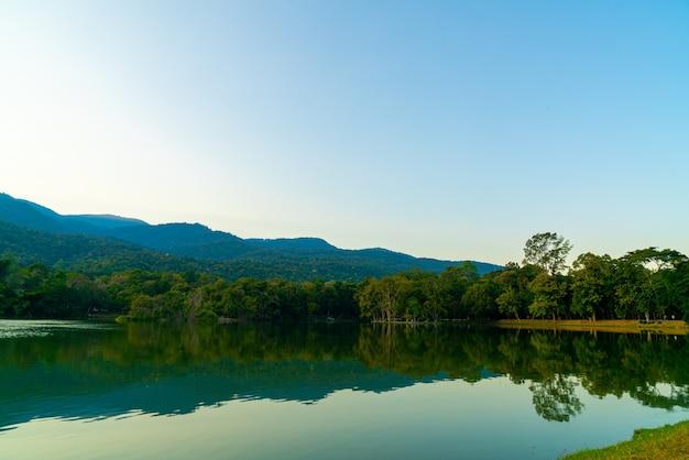 Lago ang kaew presso l'università di chiang mai con montagne boscose e cielo al crepuscolo Foto Premium