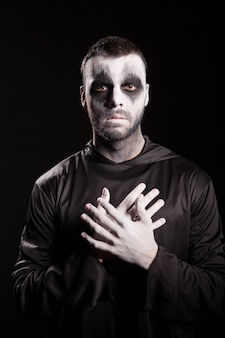 Angelo della morte guardando la telecamera su sfondo nero.