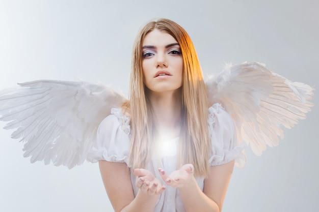Un angelo dal cielo che tiene qualcosa sui palmi. giovane, meravigliosa ragazza bionda nell'immagine di un angelo con le ali bianche.