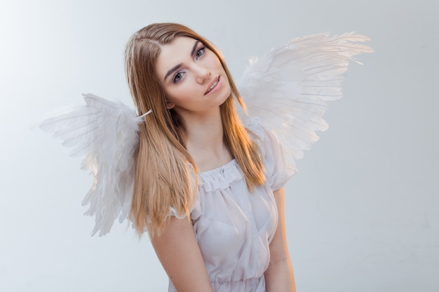 Un angelo dal cielo. giovane, meravigliosa ragazza bionda nell'immagine di un angelo con le ali bianche. primo piano del ritratto