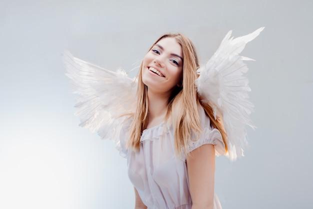 Un angelo dal cielo. giovane, meravigliosa ragazza bionda nell'immagine di un angelo con le ali bianche.