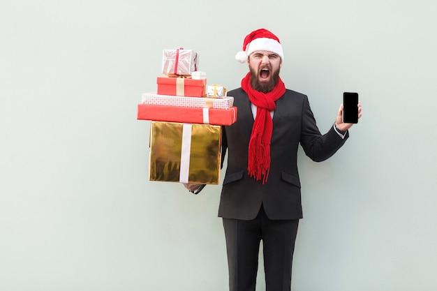 Uomo d'affari arrabbiato che tiene per mano scatola regalo e telefono guardando la telecamera con faccia ruggito