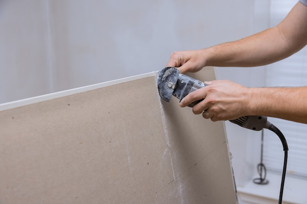 Utensili elettrici manuali ad angolo sul taglio di lastre di cartongesso