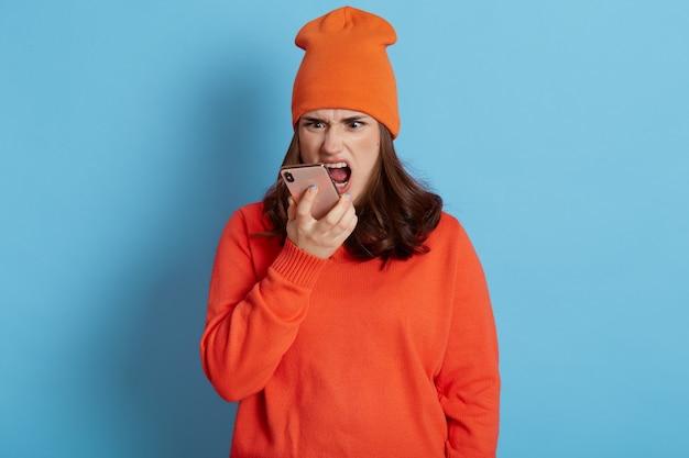 Femmina dai capelli scura aggressiva arrabbiata che grida mentre parla al telefono, esprimendo emozioni negative, indossando cappello e maglione casual, in posa isolata sopra la parete blu