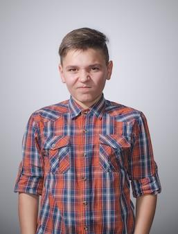Adolescente arrabbiato e aggressivo sulla superficie grigio-bianca che indossa una camicia a quadri