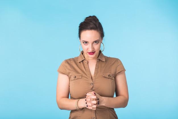 Donna aggressiva arrabbiata con espressione feroce sulla parete blu