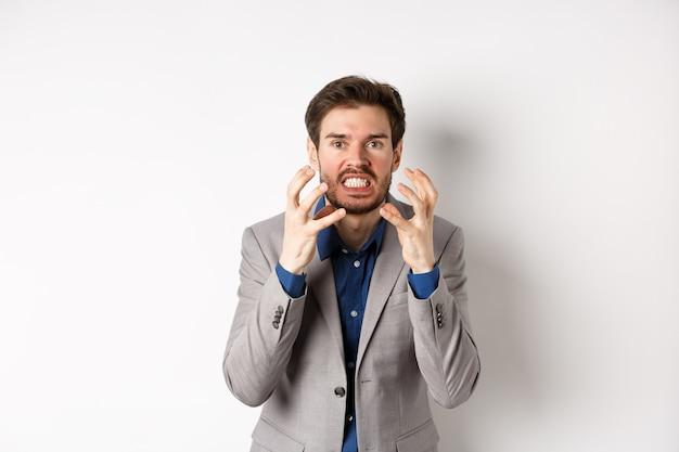 Uomo d'affari arrabbiato e infastidito vuole uccidere qualcuno, stringendo mani e denti, guardando arrabbiato con la telecamera, andando a strangolare persona, in piedi su sfondo bianco