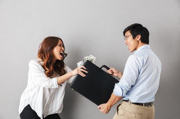 Coppia asiatica arrabbiata in piedi isolato, in lotta per una valigetta piena di banconote di denaro