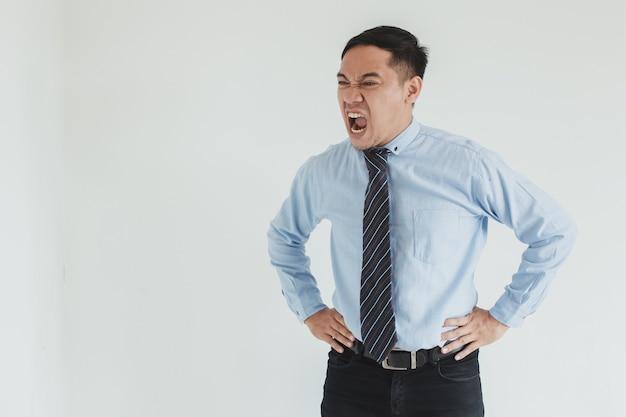 Manager di uomo asiatico arrabbiato che indossa camicia blu e cravatta che grida allo spazio vuoto su sfondo bianco