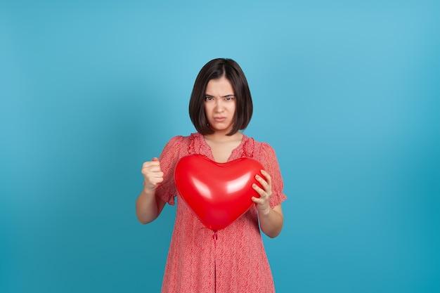 Donna asiatica arrabbiata che tiene palloncino cuore rosso e stringendo la mano in pugno