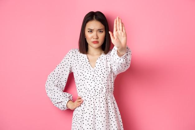 Una donna asiatica arrabbiata dice di fermarsi, allunga il braccio per proibire o disapprovare qualcosa, accigliata dispiaciuta, in piedi su sfondo rosa.