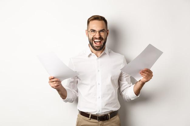 Capo arrabbiato deluso con i documenti, urlando pazzo e aggressivo, in piedi su sfondo bianco