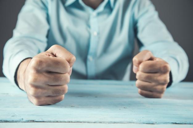 Pugno di uomo d'affari arrabbiato sul tavolo