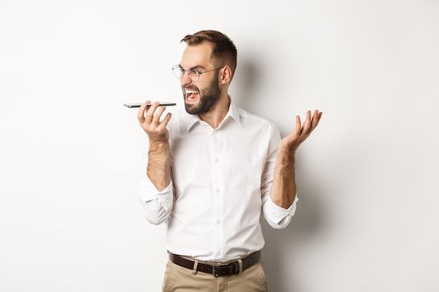 Uomo d'affari arrabbiato che grida al vivavoce, registra un messaggio vocale in uno stato pazzo, in piedi su sfondo bianco