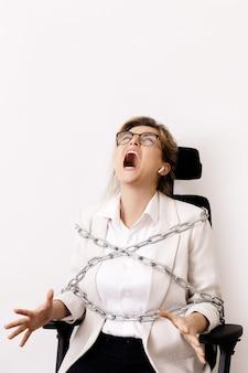 Donna d'affari arrabbiata legata alla sedia da ufficio con catene. concetto di debiti o lavoro straordinario.