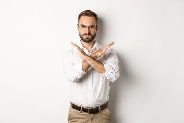 Uomo d'affari arrabbiato accigliato e mostrando croce, fermarti, dire no e proibire qualcosa, in piedi su sfondo bianco.