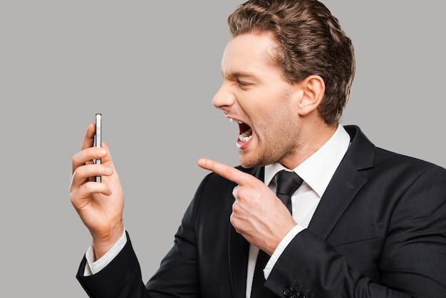 Uomo d'affari arrabbiato. giovane furioso in abiti da cerimonia che tiene in mano il telefono cellulare e gli urla mentre si trova su uno sfondo grigio