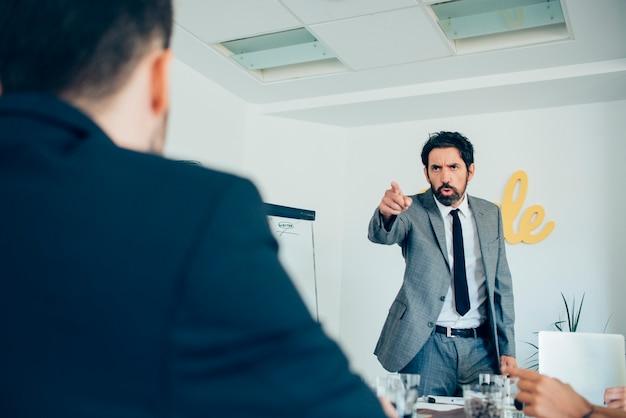 Arrabbiato uomo d'affari che punta al suo dipendente